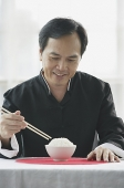 Man looking at bowl of rice on table, holding chopsticks - Asia Images Group
