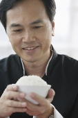 Man looking at bowl of rice in his hands - Asia Images Group
