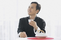 Man drinking tea, looking away - Asia Images Group