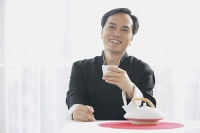 Man holding teacup, smiling at camera - Asia Images Group