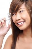 Teenage girl using eyelash curler - Asia Images Group
