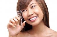 Teenage girl using eyelash curler, looking away - Asia Images Group