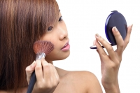 Teenage girl applying make-up, looking at compact - Asia Images Group