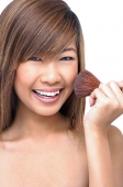 Teenage girl holding make-up brush to face - Asia Images Group