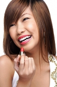 Young woman holding lipstick - Asia Images Group