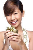 Young woman holding gift box, smiling at camera - Asia Images Group