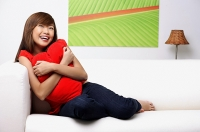 Young woman sitting on sofa, embracing pillow - Asia Images Group