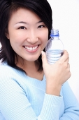 Young woman holding bottle of water, smiling at camera - Asia Images Group