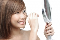 Teenage girl using eyelash curler, looking in mirror - Asia Images Group