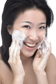 Young woman putting facial cleanser on her face, looking at camera - Asia Images Group