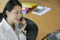 Young woman in office using telephone - Asia Images Group
