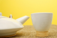 Still life with Chinese teacup and teapot, against yellow wall - Asia Images Group