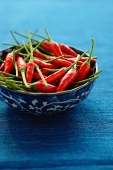 Still life of chilies in bowl on blue mat - Asia Images Group