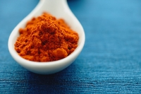 Chili powder in ceramic spoon, close- up - Asia Images Group