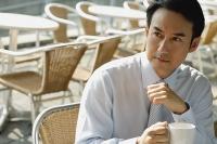 Businessman in cafe holding mug - Asia Images Group
