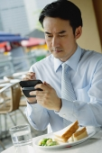 Businessman in cafe, using PDA - Asia Images Group