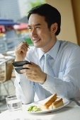 Businessman in cafe, using PDA, smiling - Asia Images Group