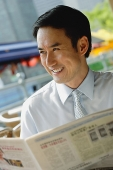 Businessman in cafe with newspaper, smiling - Asia Images Group