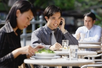 Business people at outdoor café, focus on man using mobile phone - Asia Images Group