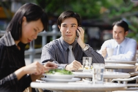 Business people at outdoor café, focus on man with mobile phone - Asia Images Group