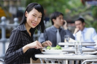 Business people at outdoor café, focus on woman in foreground, having a salad - Asia Images Group