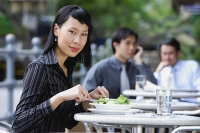 Business people at outdoor café, focus on woman in foreground, looking at camera - Asia Images Group
