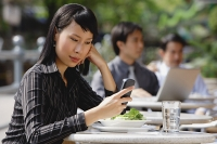 Businesswoman using mobile phone at outdoor cafe, text messaging - Asia Images Group
