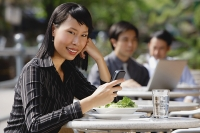 Businesswoman using mobile phone at outdoor cafe, text messaging, smiling at camera - Asia Images Group