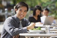 Businessman having lunch at outdoor cafe, smiling at camera - Asia Images Group