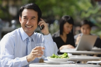 Businessman having lunch at outdoor cafe, using mobile phone, smiling - Asia Images Group