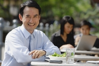 Businessman at outdoor cafe, smiling at camera - Asia Images Group
