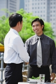Businessman at outdoor cafe, shaking hands - Asia Images Group