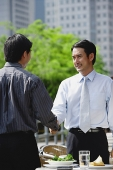 Two businessman at outdoor cafe, shaking hands - Asia Images Group