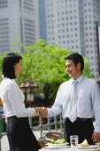 Businesswoman and businessman at outdoor cafe, shaking hands - Asia Images Group