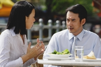 Businesswoman and businessman at outdoor cafe, having lunch, talking - Asia Images Group