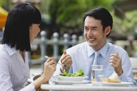 Businesswoman and businessman at outdoor cafe, having lunch - Asia Images Group