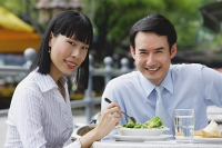 Businesswoman and businessman at outdoor cafe, smiling at camera - Asia Images Group