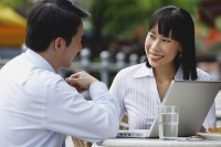 Businesswoman and businessman at outdoor cafe, with laptop - Asia Images Group