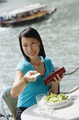 Young woman sitting at riverside cafe, holding credit card towards camera - Asia Images Group