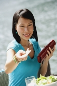 Young woman sitting at riverside cafe, holding credit card towards camera, smiling - Asia Images Group