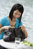 Young woman sitting at riverside cafe, looking through her handbag - Asia Images Group