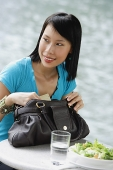 Young woman sitting at riverside cafe, looking away - Asia Images Group