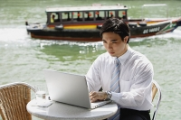 Businessman sitting at outdoor cafe, using laptop, river in the background - Asia Images Group