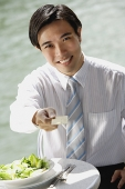 Businessman sitting at outdoor cafe, holding credit card towards camera - Asia Images Group
