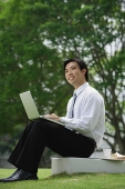 Businessman sitting in park with laptop - Asia Images Group