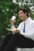 Young businessman sitting outdoors, having lunch - Asia Images Group