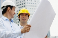 Two businessmen with blueprints - Asia Images Group