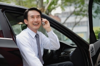 Businessman sitting in car, using mobile phone, smiling - Asia Images Group