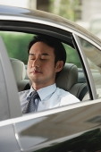 Businessman sitting in car, eyes closed - Asia Images Group