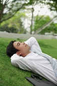 Businessman lying on grass in park, looking up - Asia Images Group